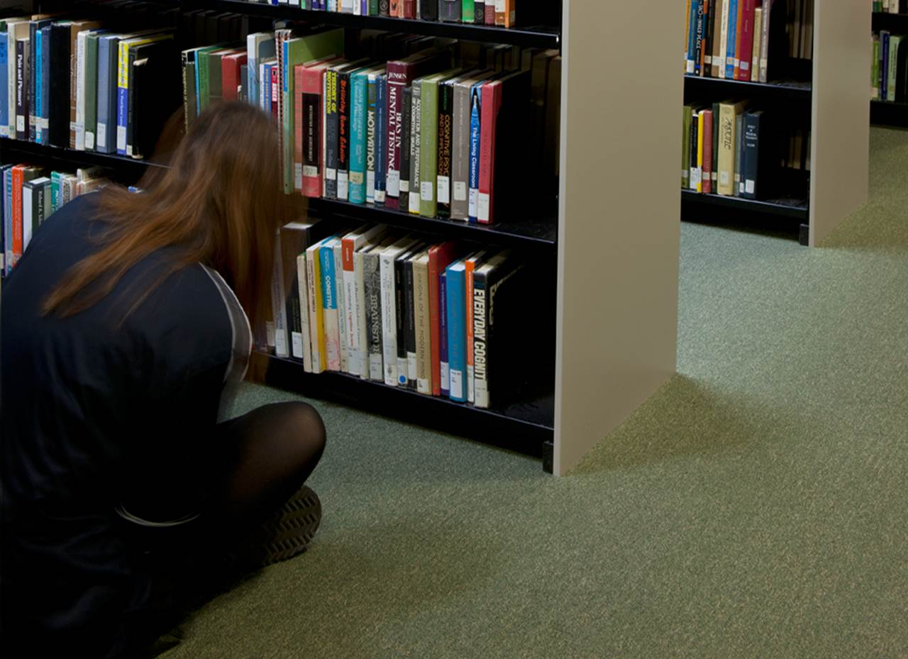 Young woman looking for a book on the library shelf