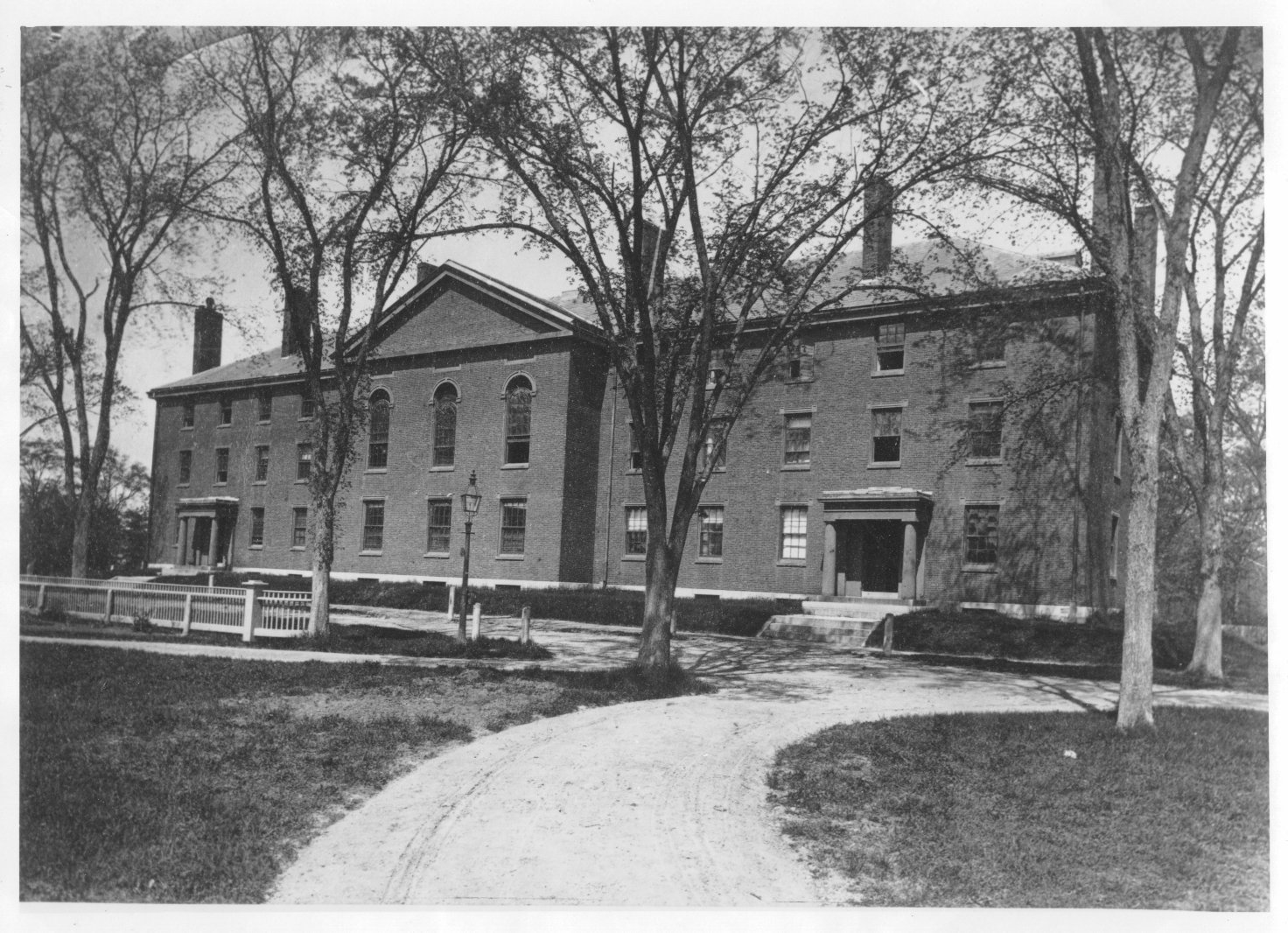 Photograph of front of Divinity Hall.   There is a picket fence in the foreground, running along Divinity Avenue,