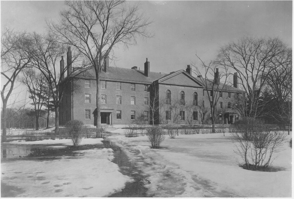 Photograph of Divinity Hall in what appears to be winter or early spring.  Melting snow is on the ground and surrounding trees are bare.