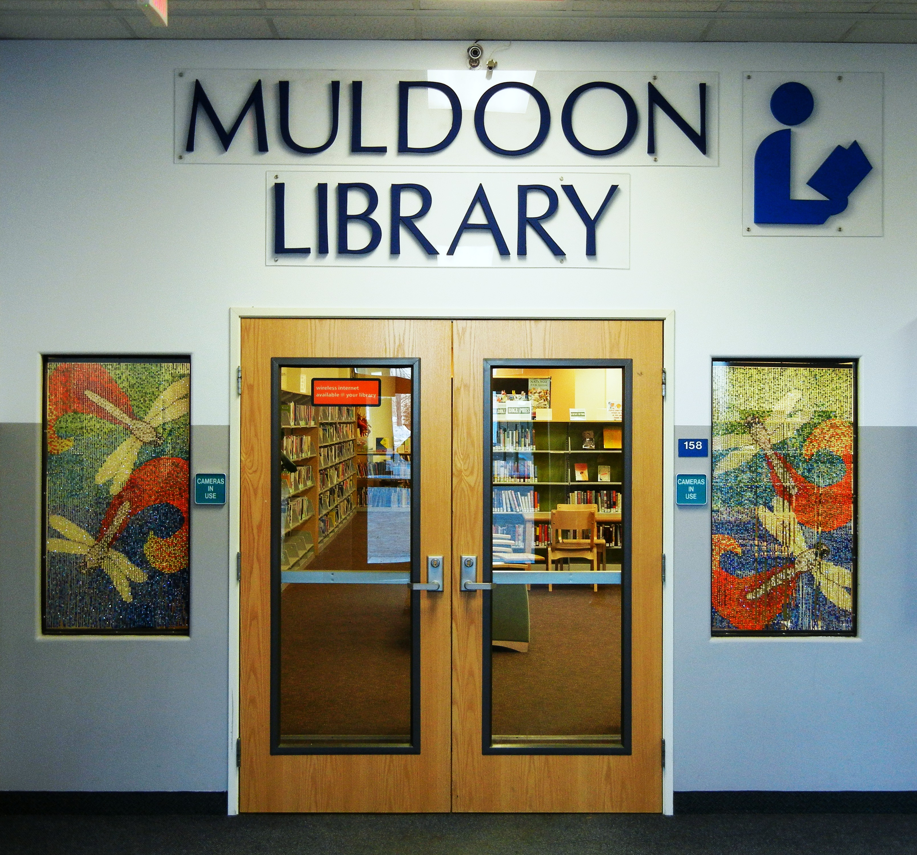 a photo of the library's front doors with Muldoon Library written above