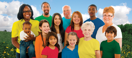 Diverse group of people looking directly at the viewer and smiling. Picture has a background of blue skies and green fields.