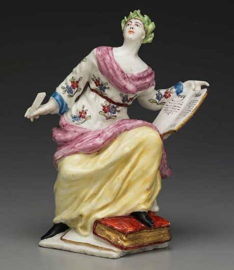 Polychrome porcelain statuette of Clio the Muse of history looking up from a book she is writing