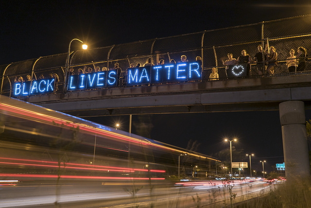 """Image of an illuminated sign over a highway, reading """"Black Lives Matter"""""""