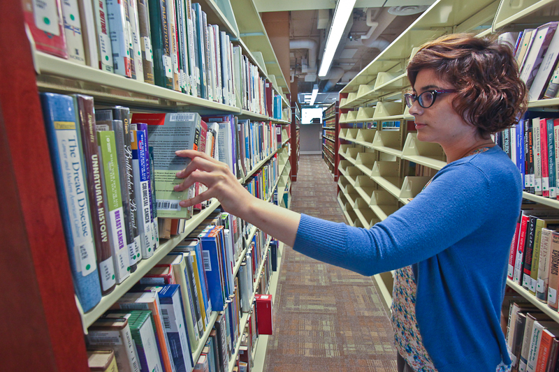 Girl pulling book from shelf