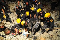 A group of helmeted aid workers pull a crying child out of rubble.