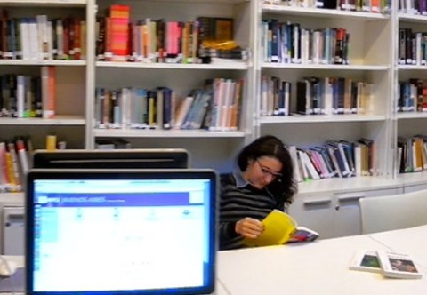 Student reading a book in the library with computers next to them.