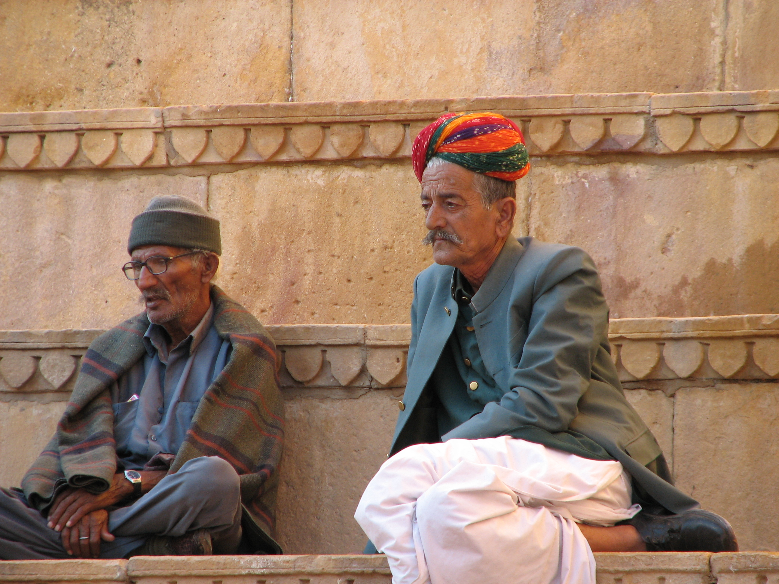 Two men sitting at Jailsalmer Fort, Rajasthan. One is wearing an orange, red and green traditional Rajasthani turban while the other person is wearing a regular woolen hat. copyright 2006 David Magier