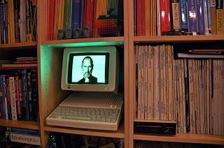 Bookshelf grid with some shelves lined with colored spines and the central shelf containing a glowing Apple IIc computer with Steve Jobs in the screen.