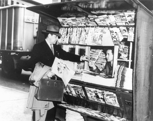 Image of a man buying a paper at a newsstand