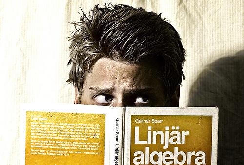 En man som är gömd bakom boken