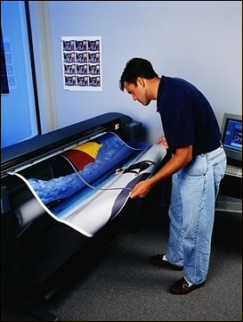 Man looking at a full-color printed image coming off a large scale printer.