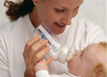 Woman giving bottle to infant.