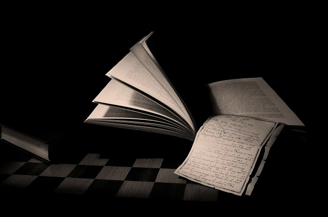Pixabay image of books and paper in darkness
