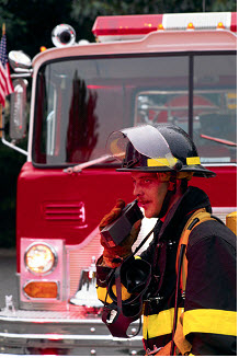Firefighter on walkie talkie in front of fire truck