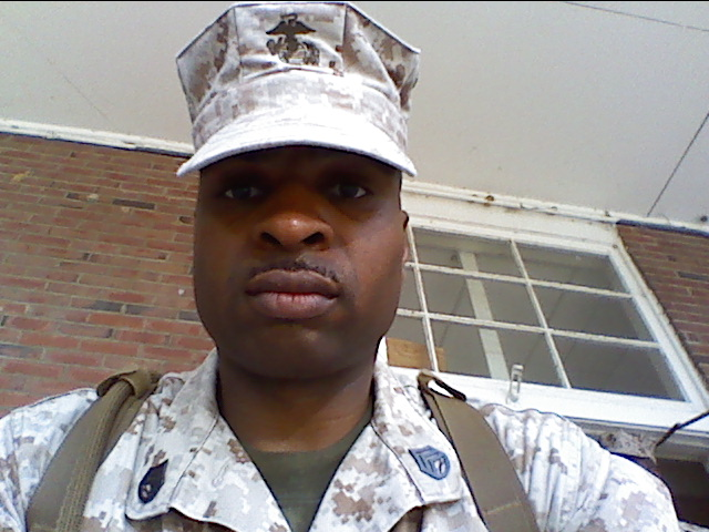 Photo of Edwin Julien, African American man in military-looking cap and shirt.