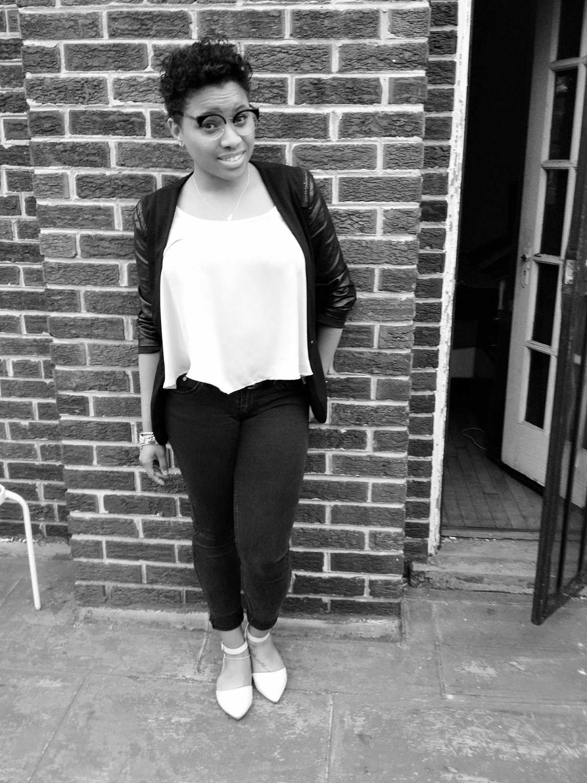 Photo of Danyelle Brandon, a young African American woman with glasses & short hair, standing next to brick building.
