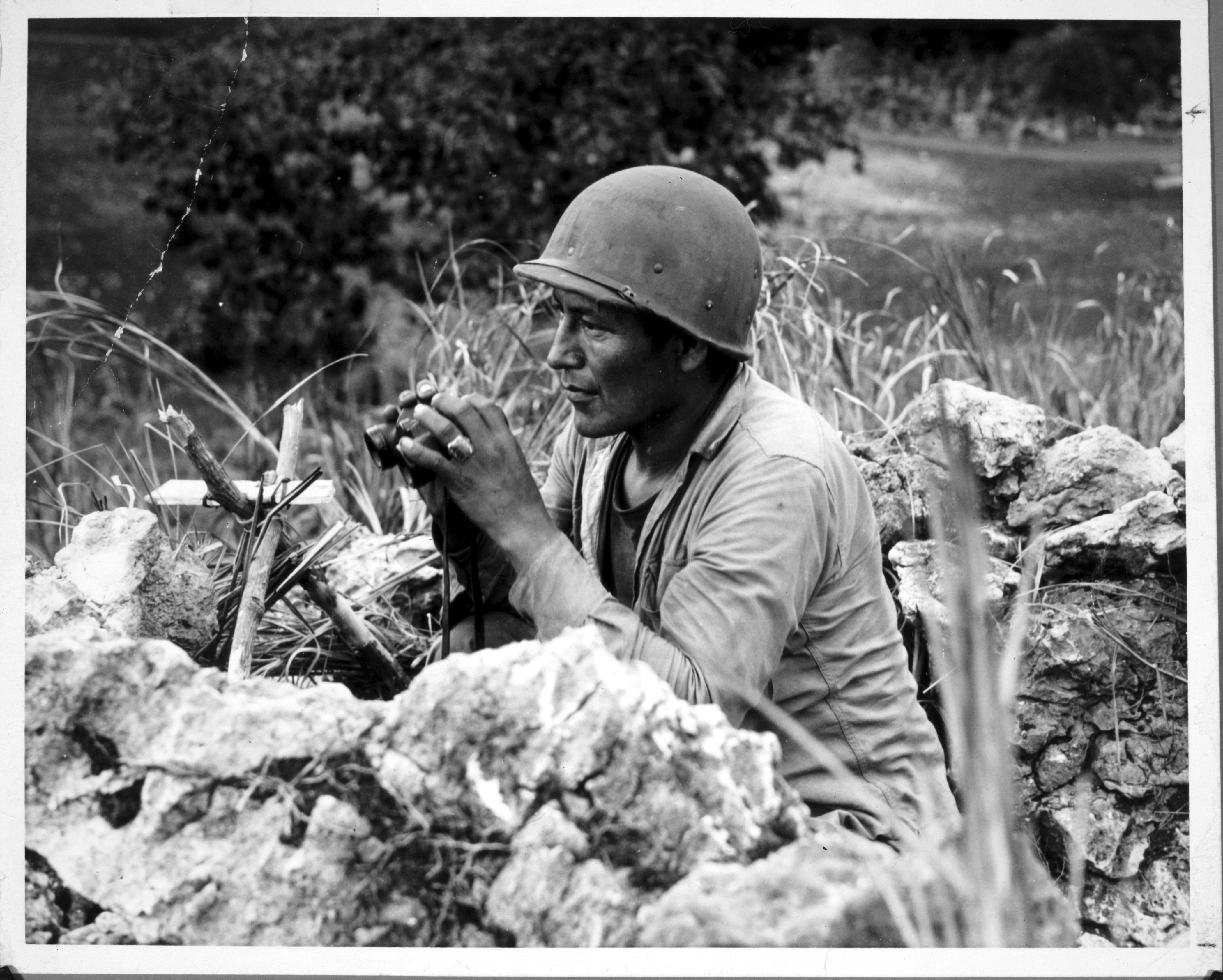 Navajo Code Talker Carl Gorman tracks enemy movements on the island of Saipan in the Marianas, June 27, 1944, US National Archives.