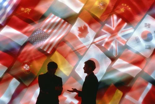Two men talking in front of a wall of flags