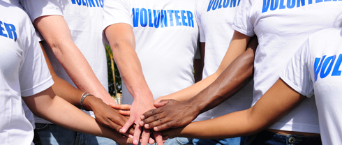 image of people with white tshirts that read volunteer all putting their hands in the middle of a circle