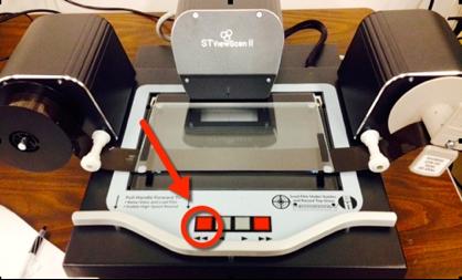 Far left red rewind button on microform machine