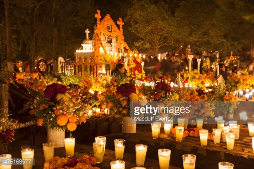 Cemetery site decorated for Day of the Dead with candles, marigolds, and plates of food.