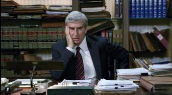 "Jack McCoy, looking perplexed and dishelved, from TVs ""Law and Oder"" sits in front of shelves of books."