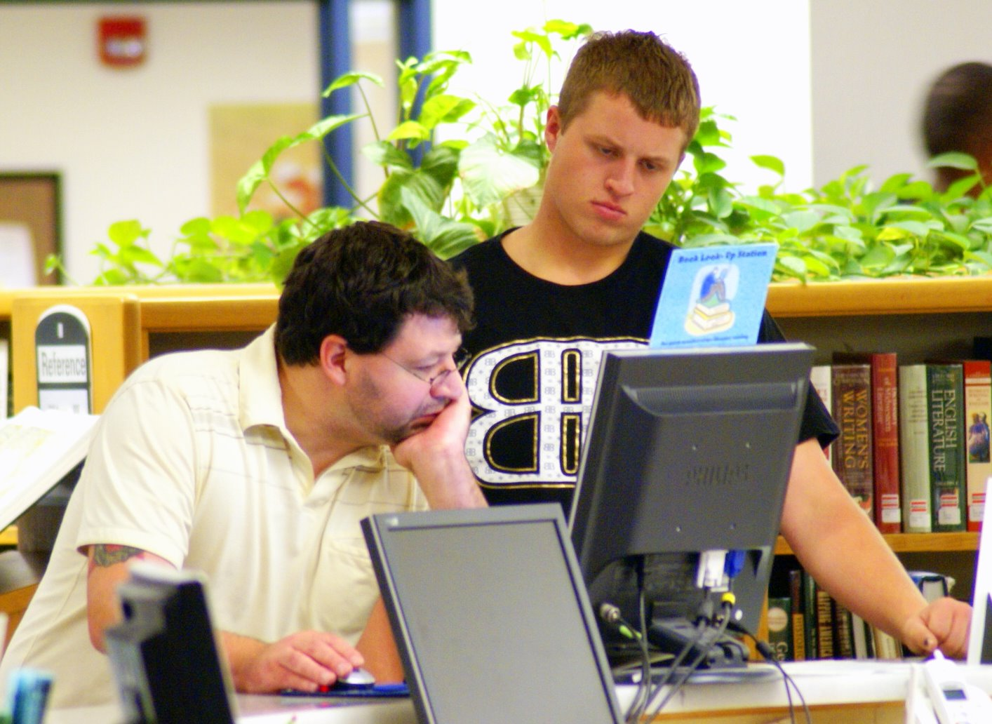 Librarian helping student at computer