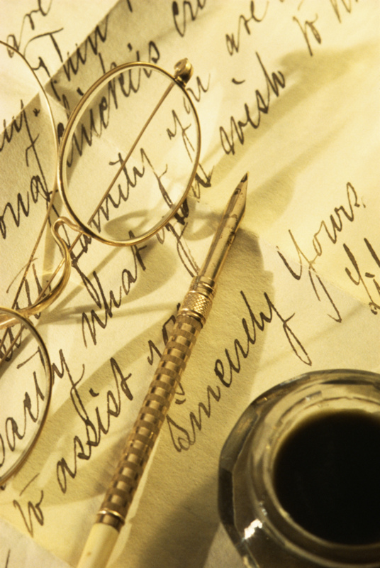 eyeglasses, ink, and quill atop handwritten paper