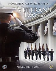 "A person in uniform salutes a group of people bearing flags in front of a colonnade. Text reads: ""Honoring all who served. Veterans Day 2009."""