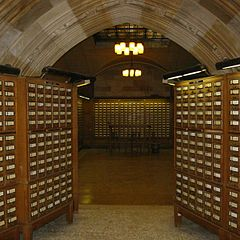 Many cabinets of the Yale Library card catalog near an arch way.