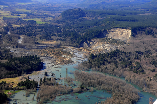 Image of the Oso, WA landslide showing a large mass of debris covering the river and homes.