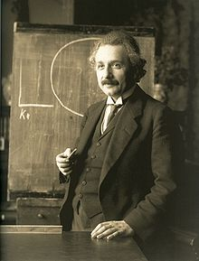 Albert Einstein in front of a chalkboard