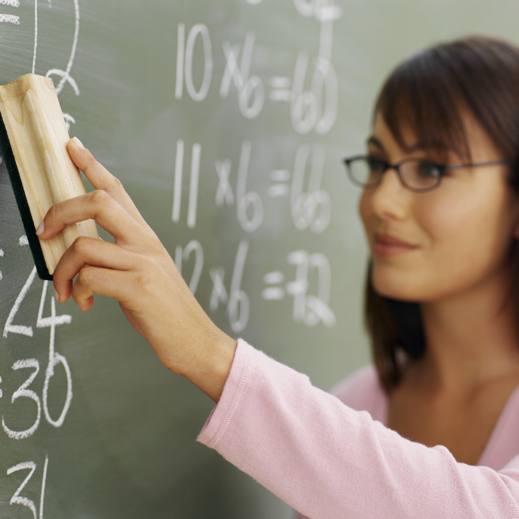 Teacher at chalkboard with eraser.