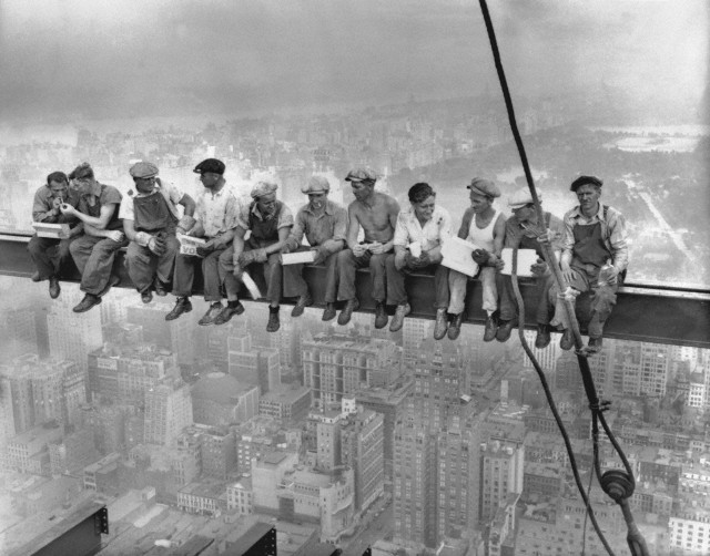 men eating lunch on a girder during skyscraper construction