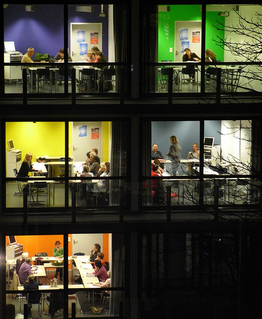 photograph of people working in a multistory building as seen through the windows from the street below