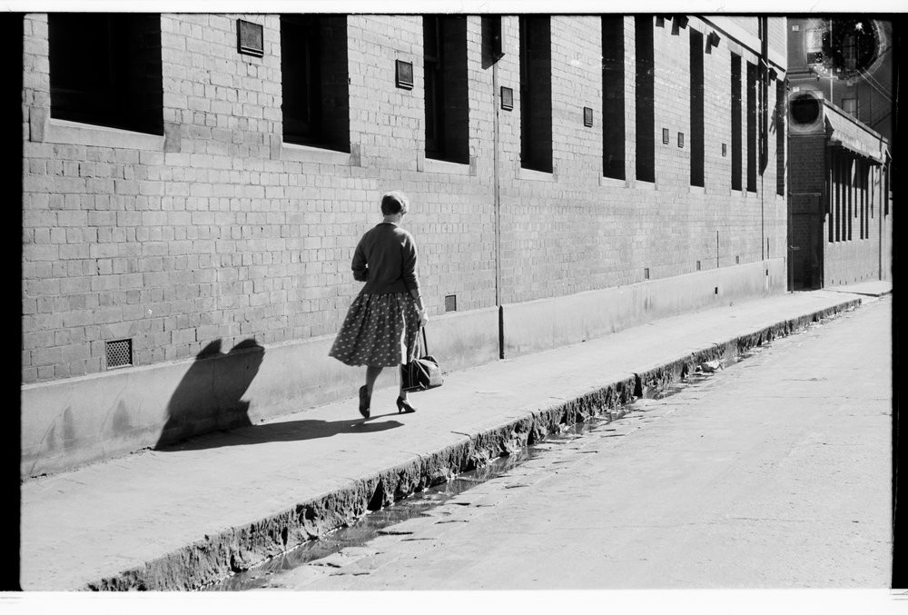 Woman walking along footpath next to brick building, Mark Strizic, ca 1950-1959, H2008.11/1333