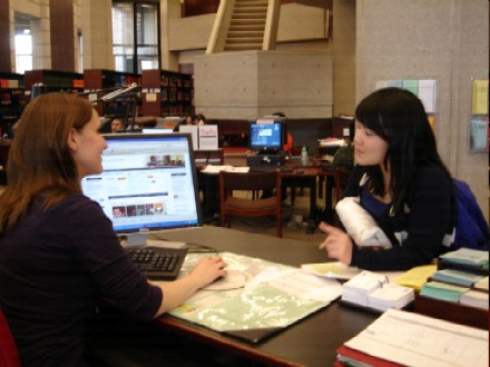 student and librarian talking on the reference desk