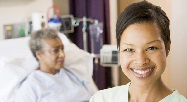 Smiling nurse with patient in hospital bed behind her.