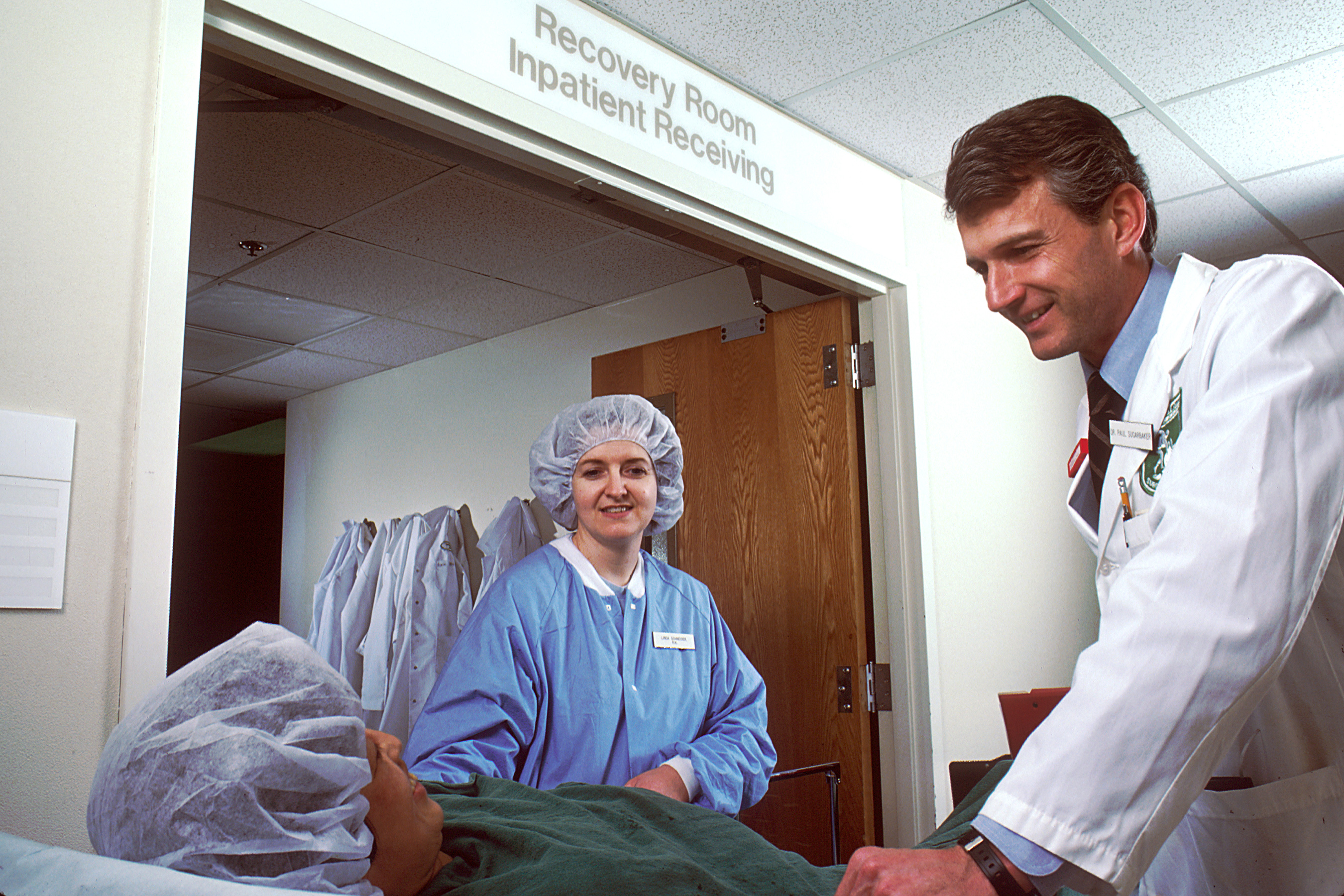 Male medical person in lab coat with female medical with surgery gown and hair covering next to patient on gurney in sheet and hair covering