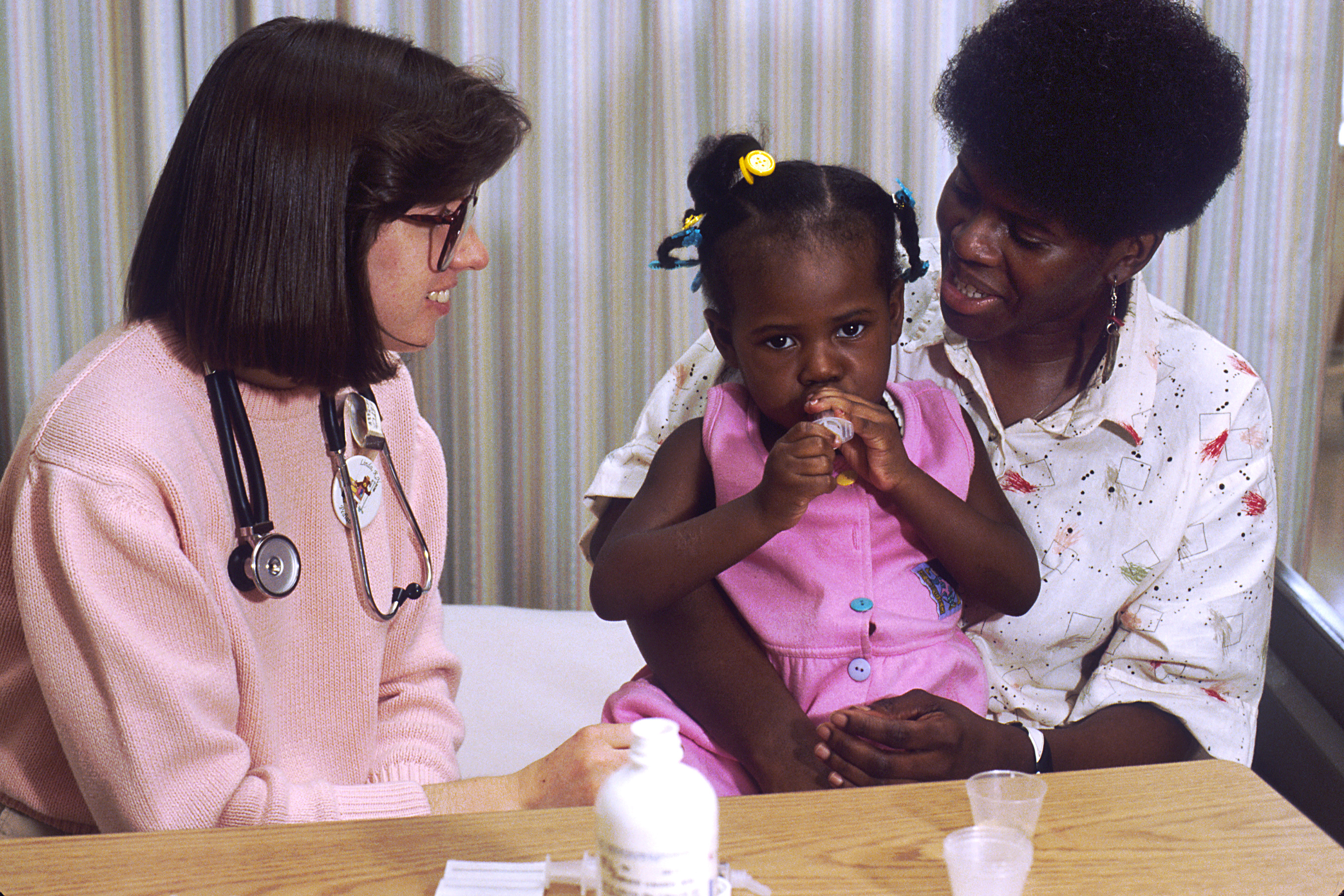 One medical woman with stethoscope next to a black mother with child on lap taking medicine