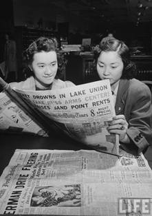 Two women reading a newspaper in the Congressional Library's Newspaper Reading Room.