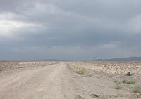 Gravel road heading straight into the desert.