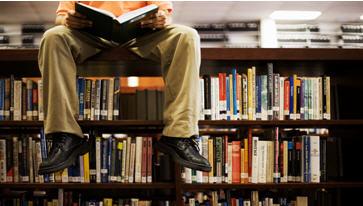 person sitting on bookshelf