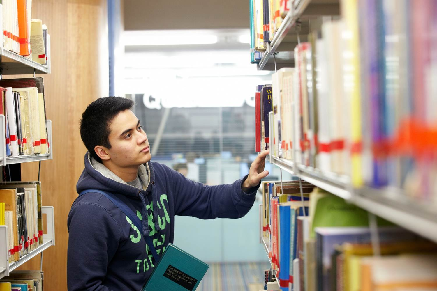This is an image of a person looking on the library shelves for books.
