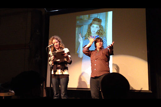 photograph of a performer and an interpreter at a poetry slam