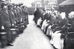 Female firefighters practise a drill at a London workhouse for elderly women