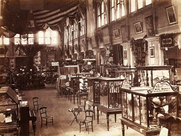 Photograph, intercolonial exhibition, 1875. View of Main Hall. Looking south, depicting glass cases containing objects of display, and paintings hung on walls