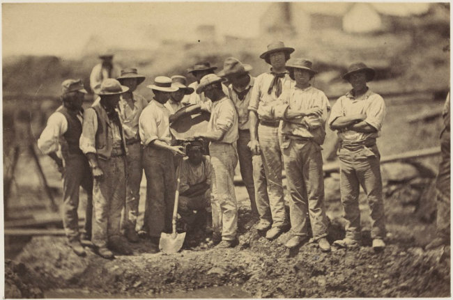 Photograph, group of men standing at diggings, washing out a good prospect