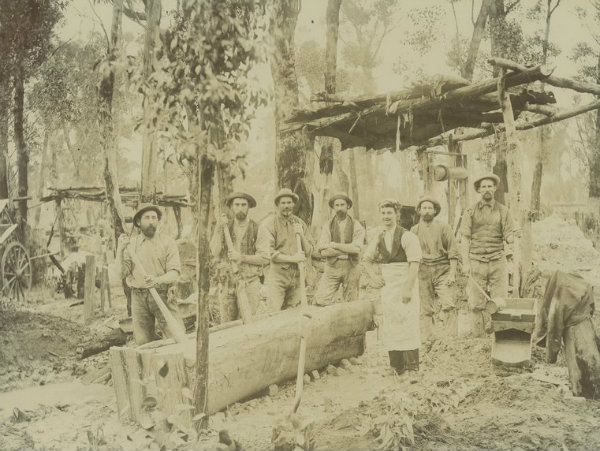 Photograph, View shows seven men standing around gold cradle, with mine shafts and trees behind them.