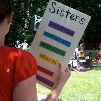 "woman holding a sign that says ""sisters"" with text in rainbow colors below"